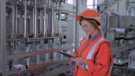 revisione : factory Engineer female into helmet uses digital tablet to control work of belt line for bottling mineral water in bottles at plant Filmati Stock