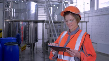 overall : forceful woman at factory, portrait of engineer female into hard hat and coveralls with computer tablet making calculated decisions at work
