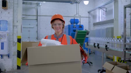 revisione : hard work women in factory, smiling strong female into helmet and coveralls carries big heavy box with plastic bottles through plant enterprise Filmati Stock