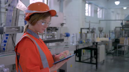 overall : heavy female work, Factory specialist girl into hard hat uses computer tablet for revision and controls hardware operation in plant