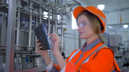 revisione : job engineer, smiling Factory master woman into hard hat uses tablet laptop and making calculated production decisions at plant Filmati Stock