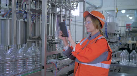 равный : modern technologies in production, happy Factory specialist woman into hard hat uses tablet laptop and making calculated production decisions at plant