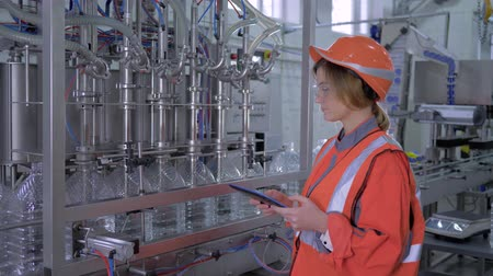 revisione : modern technology at factory, Industry worker female into helmet uses digital tablet to control operation of conveyor line for bottling mineral water in bottles at factory Filmati Stock