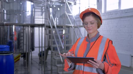 revisione : powerful woman at plant, factory worker female into hard hat and overall with computer tablet making calculated engineering decisions at factory