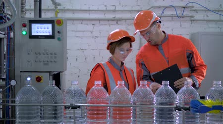 revisione : Engineers guy and girl into helmet and working clothes near conveyor line for bottling mineral water in plastic bottles during inspection and quality control of production at plant.