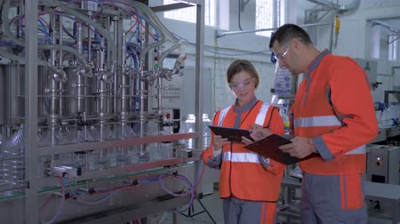 revisione : factory profession, young woman and man Industry workers into coveralls with digital tablet in hand near automatic conveyor line with bottling of mineral water in plastic bottles on production plant