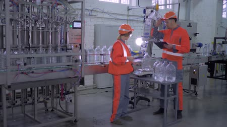 égalité hommes femmes : factory workers man and female into helmet and overall near conveyor line for bottling mineral water in plastic bottles during inspection and quality control of production at plant.