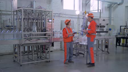 равный : quality production control at factory, experts men and woman into hard hat and workwear near conveyor line for bottling mineral water in plastic bottles during inspection at plant industry Стоковые видеозаписи