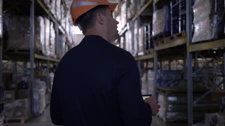 supervisor : businessman in hard hat and suit walking through warehouse makes notes on the tablet