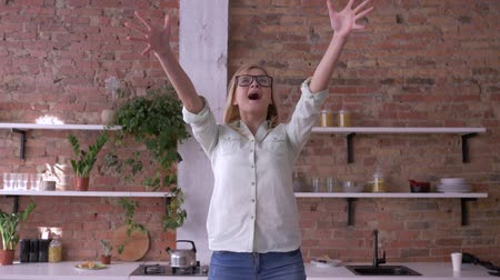 хорошее настроение : cheerful office female worker with glasses throwing paper documents and celebrating success of project in the kitchen Стоковые видеозаписи