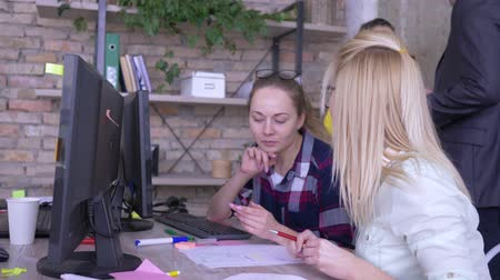 spolupracovníci : young female colleagues solving problems and discussion work related matters in creative office