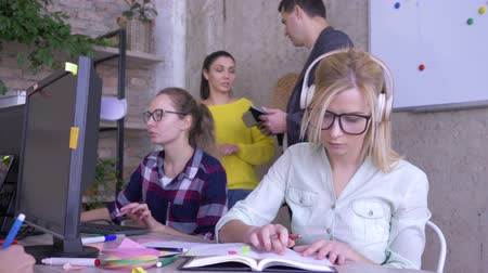 spolupracovníci : people at work, young team is working in the modern office on a business plan then girl looks at the camera and smiles
