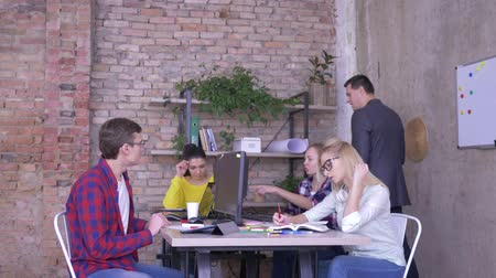 spolupracovníci : manager in suit trains new workers in the office, business group communication at a table