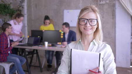 spolupracovníci : happy female office worker in glasses making notes on paper and then smiling at the camera Dostupné videozáznamy