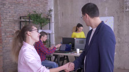 spolupracovníci : director and new workwoman shake hands when meeting on background of office employees at the table with computers