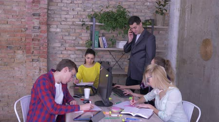 spolupracovníci : day to day work, businessman with mobile phone reports good news and gives five to his employees then they folded hands and raised in modern office Dostupné videozáznamy