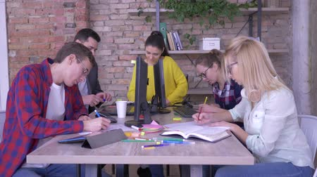 spolupracovníci : active young office workers write notes with ideas in notebooks and colored stickers sitting at the table in modern office