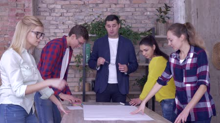 spolupracovníci : Creative team in modern office, Successful corporate executive guy with collaborators working on development project of new business ideas on big drawing paper at table Dostupné videozáznamy