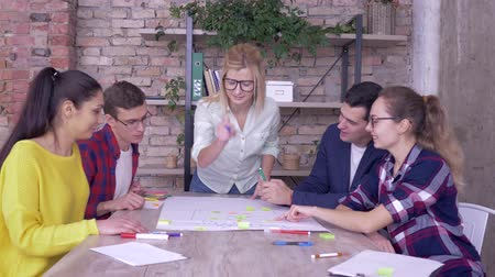 spolupracovníci : successful business deal, joyful office men and women giving thumbs up during winning work on new project on big paper with colored stickers in modern office Dostupné videozáznamy