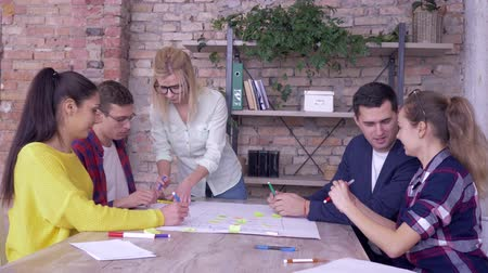 spolupracovníci : successful business project, happy office team giving positive gesture during triumph work on new project on big paper with colored stickers in modern office