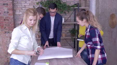 spolupracovníci : Successful business team in modern office, young mentor man with Colleagues working on development project of new business ideas on big drawing paper on table