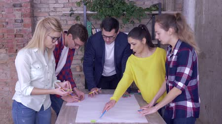 spolupracovníci : Successful working team in modern office, young boss male with associates discussing on development project of new business ideas on big drawing paper at table