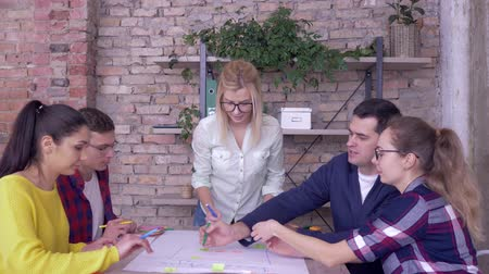 spolupracovníci : teamwork in modern office, Successful business people working on development project of new business ideas on big drawing paper at table Dostupné videozáznamy
