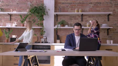 spolupracovníci : crazy triumph at work, Successful office man into glasses learns good news in laptop and rejoices with business team hugging and throwing documents into air at kitchen in modern office