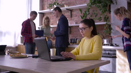 spolupracovníci : modern office, business female wearing glasses works on laptop while collaborators eat sandwiches and communicate during lunch in cuisine at modern office