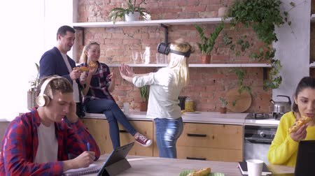 jelenleg : modern technology in office, young female with Virtual reality helmet plays games while collaborators eat and chat while working at cuisine in Business center