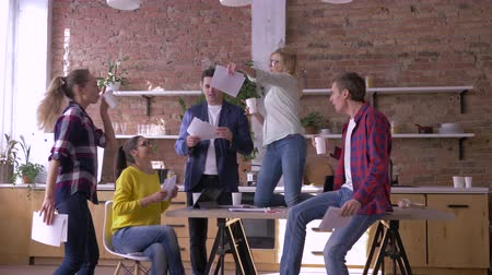 удачливый : office party, crazy creative team of workers men and women having fun while job in kitchen in modern office and throwing documents into air