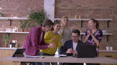 spolupracovníci : successful business deal, office male into glasses learns good news in computer and rejoices with Colleagues hugging and throwing documents into air in cuisine at modern office