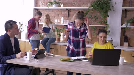 spolupracovníci : working team of successful young businesspeople are eating and working with tablets and laptops in kitchen during making of new creative project in modern office