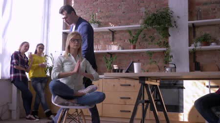 spolupracovníci : Young calm office worker girl relaxing and meditating at workplace sitting in yoga pose with eyes closed and not listening to screaming boss man in modern business center. Dostupné videozáznamy