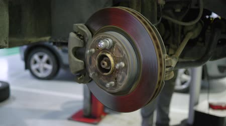 handling : auto repair shop, maintaining car wheel brake disc at repair service station close-up