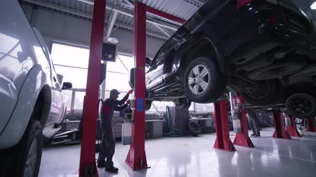 ремонт : KHERSON, UKRAINE - FEBRUARY 26, 2019: Auto business, pro technician Man raises vehicle on lifts for repairing in car service station Стоковые видеозаписи