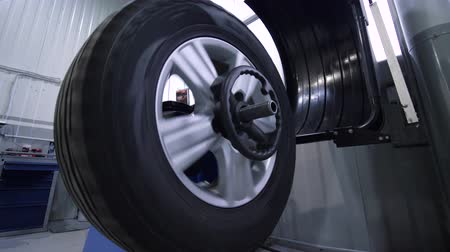 vyvažování : KHERSON, UKRAINE - FEBRUARY 26, 2019: wheel balancing in car service station closeup wheel spinning on equipment during repair