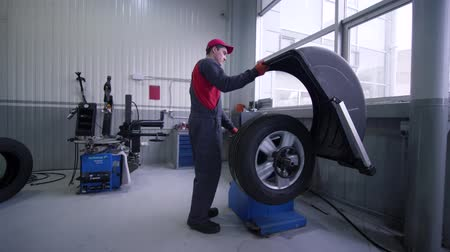 ремонт : KHERSON, UKRAINE - FEBRUARY 26, 2019: wheel balancing, professional mechanic male repairs car wheel in auto workshop Стоковые видеозаписи