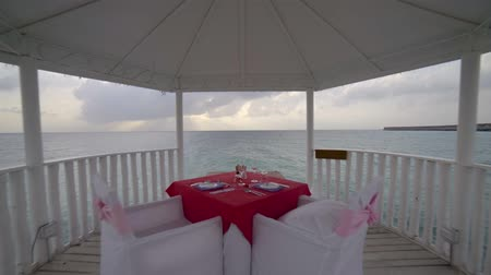 exotic dishes : romantic Atmosphere at tropical beach, bungalow with glasses and dishes on table in sea against water and sky