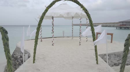registration : Wedding arch decorated with flowers on ocean beach against sky and water at exotic summer resort