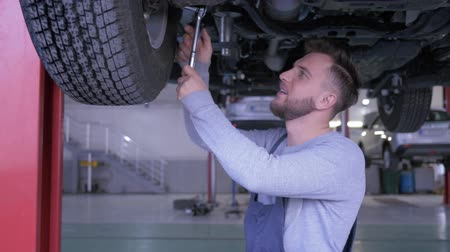 wrench : portrait of handsome mechanic in boilersuit on service station works with a key under the bottom of the car Stock Footage