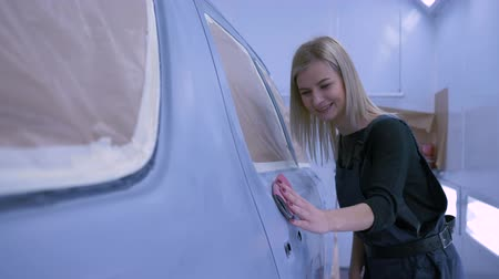 ремонт : Auto business, smiling car painter female polishes automobile after paint by hand at paint chamber during repair work at service station