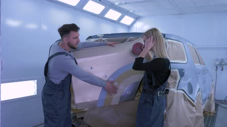 handling : car painting, auto mechanics man and woman choose color to paint vehicle during repair work in paint chamber Stock Footage