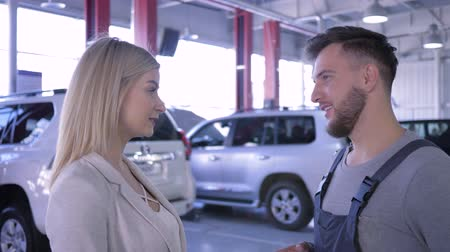 handling : portrait of smiling mechanic male and consumer woman communicates about auto repairs at workshop Stock Footage