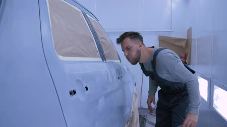 ремонт : professional Auto painter guy sanding car after paint by hand at paint chamber during repair work at service station Стоковые видеозаписи