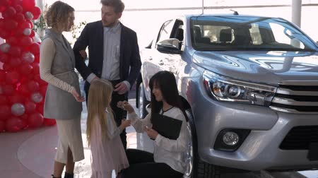 consigliare : successful purchase of family auto, friendly female car seller puts keys in hands of little girl with parents to new automobile owners at auto show center