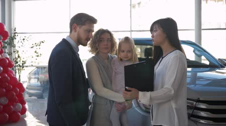 продавщица : vehicle buying, happy couple with little child informs with car consultant on purchase of new family automobile at sales showroom