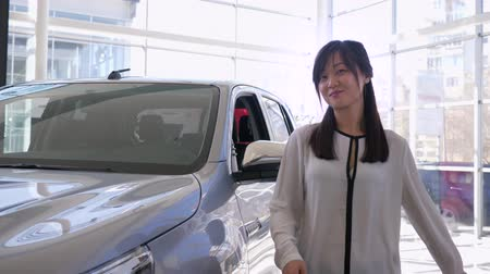 продавщица : Auto business, portrait of smiling saleswoman pats car with pleasure and shows keys to new automobile for sale in sales center close-up