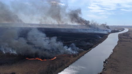 extinguishing : emergency disaster in nature, large Wildfires fast moving by dry field with black smoke going up to sky near river, bird eye view