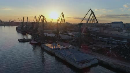 moorage : international trade, commercial berth with lifting cranes for loading and unloading of vessel of international trade on Sea coast against blue sky in Sunset and shiny water, Top view